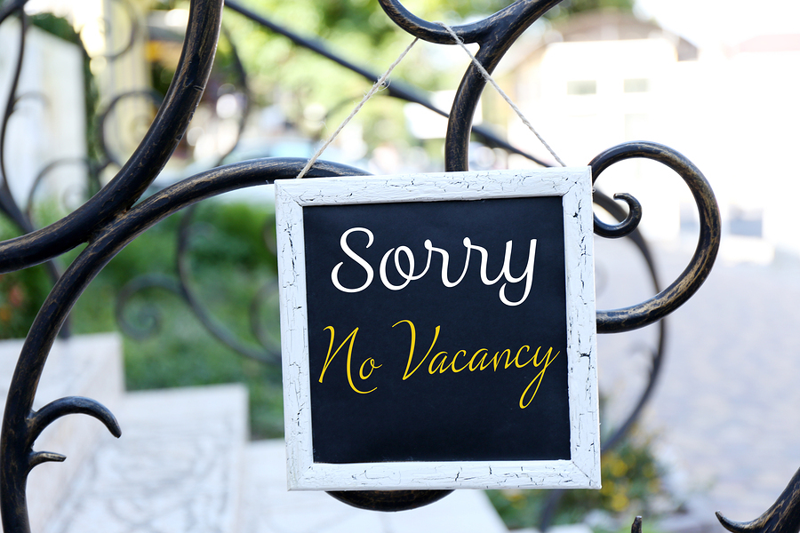 Signboard with text Sorry No Vacancy near hotel